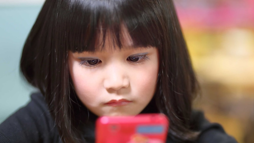 A young girl looks at a smartphone.