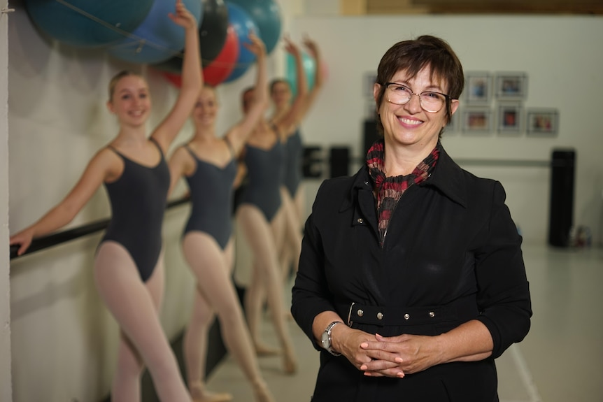 A woman with short brown hair wearing a black jacket smiles at the camera, in the background 4 ballet dancers in blue leotards