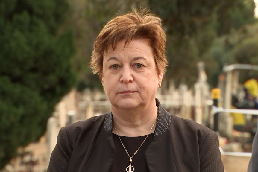 A portrait photo of a woman in a cemetery.