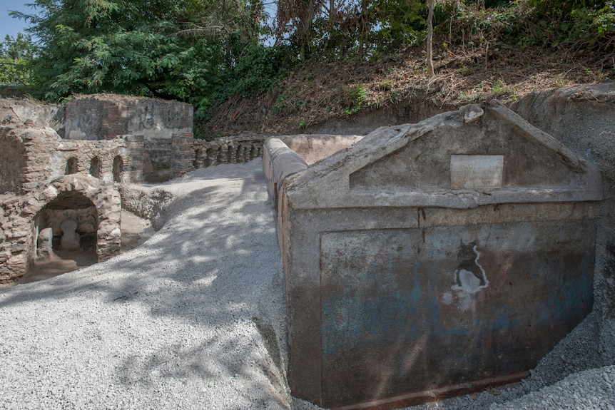 Landscape of Pompeii shows tomb stone among rock and silt