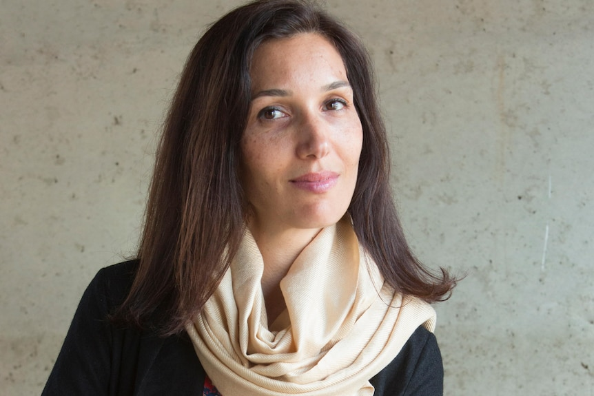 Delphine Minoui, with shoulder-length brown hair, scarf and slight smile, sits on a chair with arms crossed over knee.