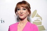 A portrait shot of Kathy Griffin standing in front of a backdrop showing the Grammys logo.