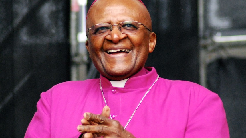 A photo of Desmond Tutu wearing purple clerical robes and spectacles, smiling