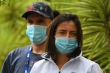 Tennis players wearing masks line up for COVID-19 tests outside, surrounded by plants.