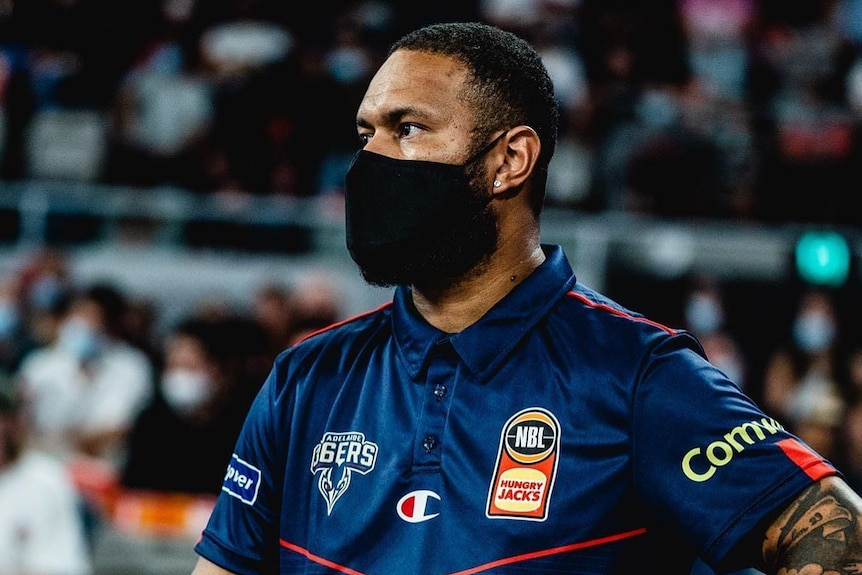 Junior Viranatuleo  standing side of court wearing a covid mask and wearing a 36'rs jersey