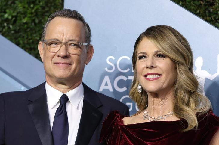 Tom Hanks, left, looks slightly to the right with a frown on his face next to wife Rita Wilson, right, who smiles.