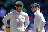Tim Paine and Steve Smith stand looking off to one side, both standing with their hands on their hips
