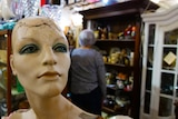 A mannequin head sitting in an antique shop.