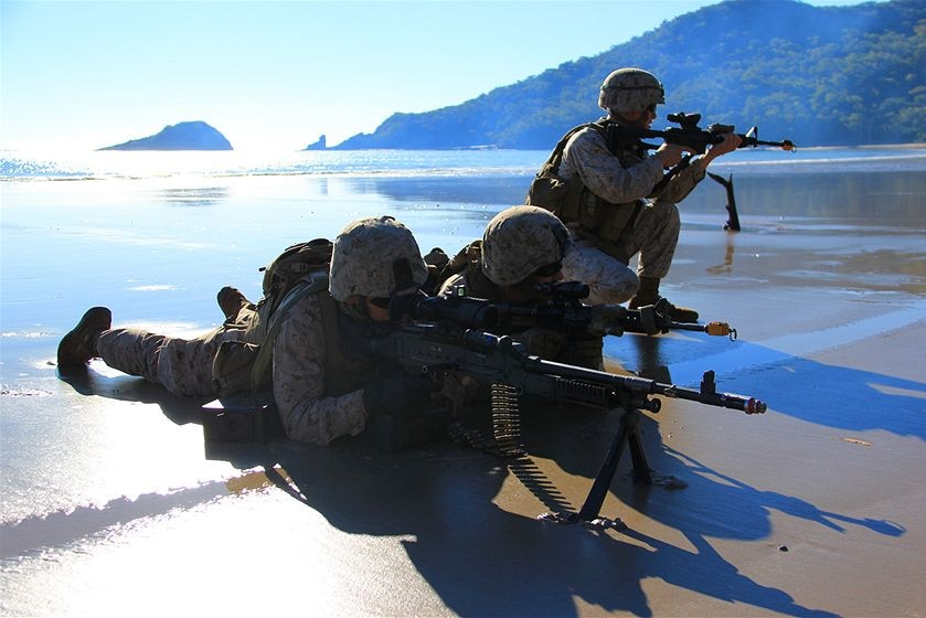 Military troops lie on a beach with guns pointed.