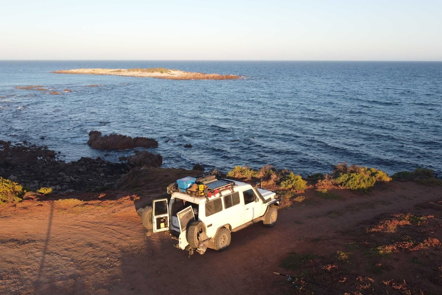 A $WD parked with the back door open on a coastal road next to the ocean.