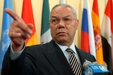 Colin Powell, standing in front of flags, points to a reporter during a news conference.