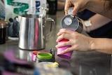 A barista pours milk into a reusable coffee cup