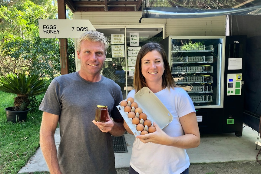 The couple stand in front of a vending machine loaded with eggs and honey.