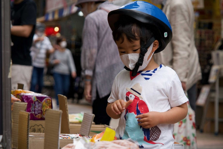 A child in a face mask and bike helmet examines food at a stall in Tokyo