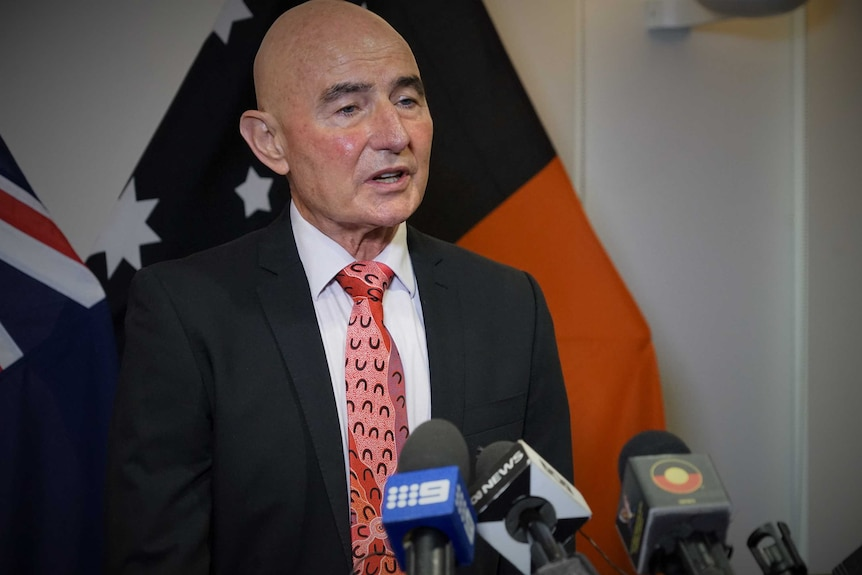 Hugh Heggie is wearing a suit and tie and standing in front of a NT flag. He is talking at a press conference.