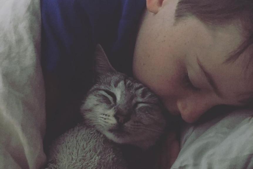 A boy snuggles asleep with a cat