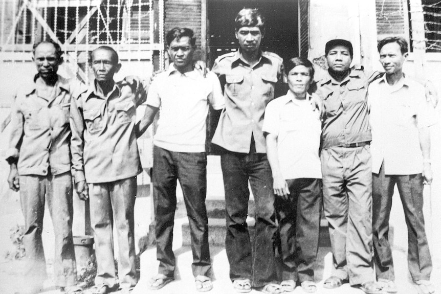 A black and white photo of the seven adult survivors of S-21 pictured standing side by side.