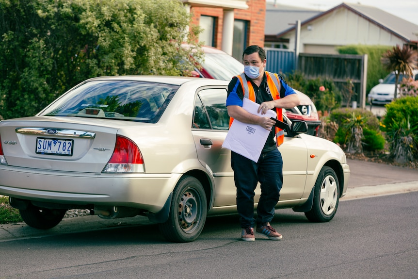 A man in an orange high-vis vest carries an envelope as he stands in front of a car on a suburban street.