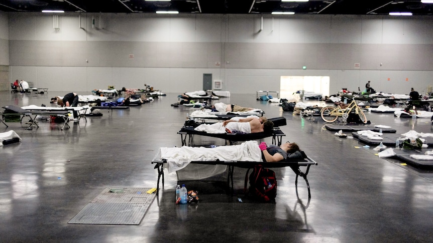 A group of people lie on spaced out beds in an empty room.