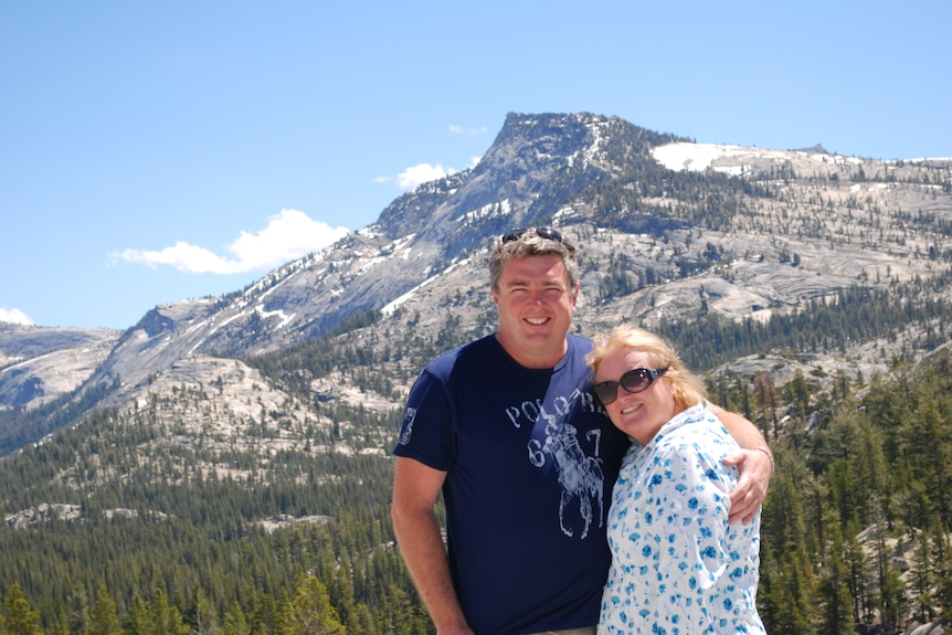 A middle-aged man and woman stand in front of a mountain with snow.