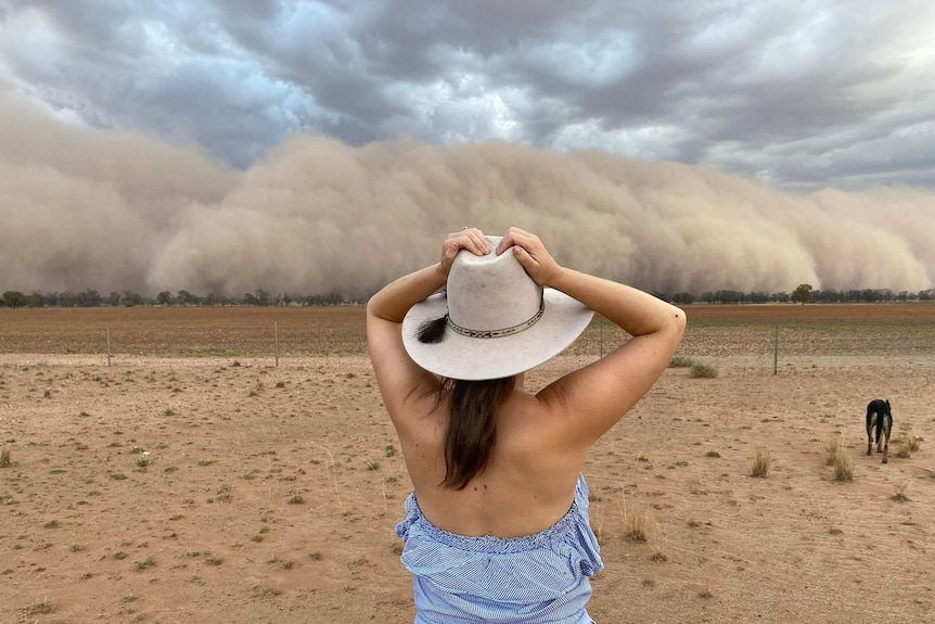 A woman in an akubra hat with a dog standing in a very dry paddock as a wall of dust approaches