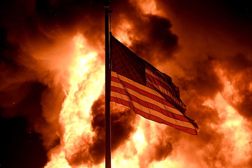 Flames engulf the Community Corrections Division building as an American flag flutters on a pole in Kenosha.
