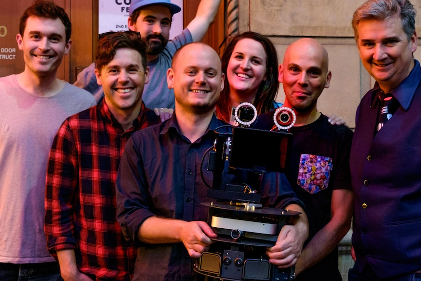 Six men and one woman stand smiling behind a robot named LOL-BOT