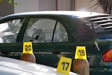 A green car with damaged windows and police incident identification numbers