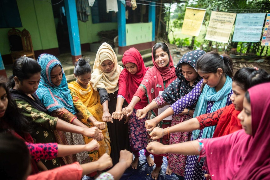 A group of young women standing in a circle putting their hands in the middle in Sylhet, Bangladesh.