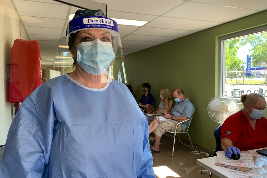 The CEO of a clinic stands indoors in full protective gear.