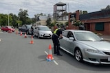 A line of cars funnel through a checkpoint manned by police.