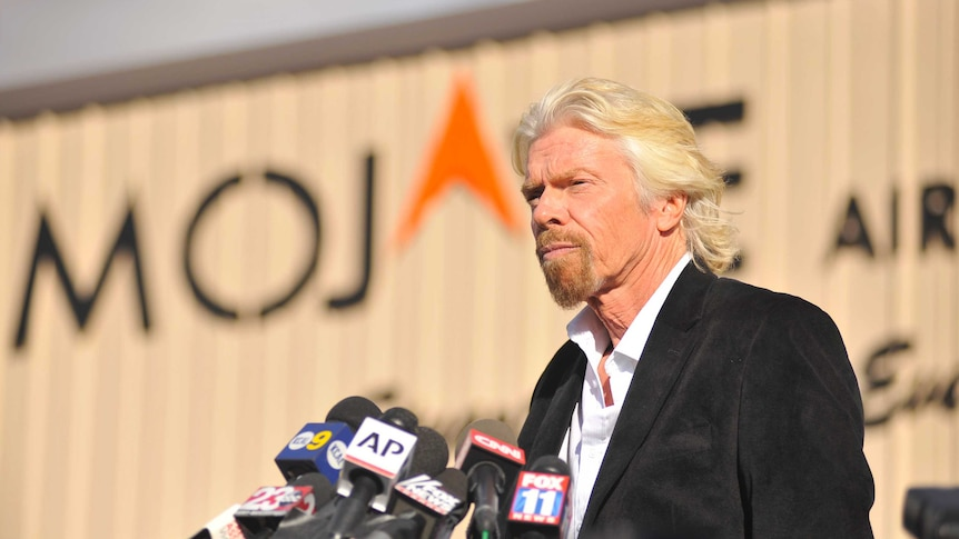 Richard Branson standing at a podium about to do a press conference.