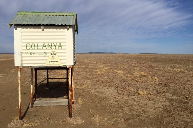 Colanya station sign with droughted land in the backdrop.