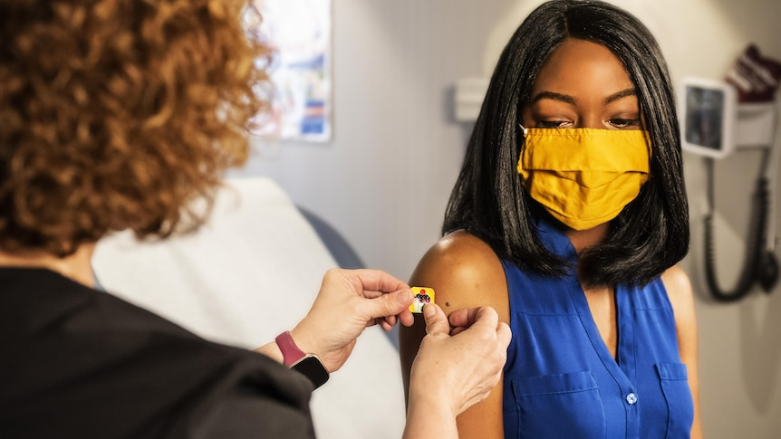 Woman in a yellow mask having a small bandaid placed on her arm.