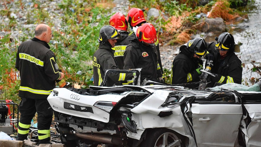 Rescuers work to recover an injured person from a crushed car.