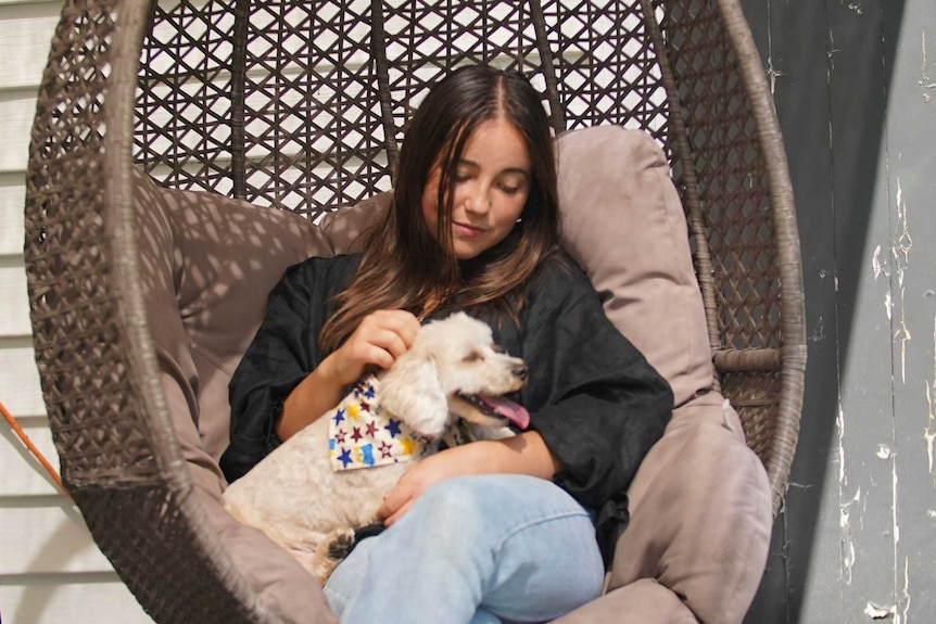 A woman sits in a chair with a dog on her lap.