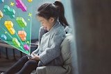 Young girl plays with phone with graphics of tetris coming out of it to depict what to do if you're worried about kids' gaming.