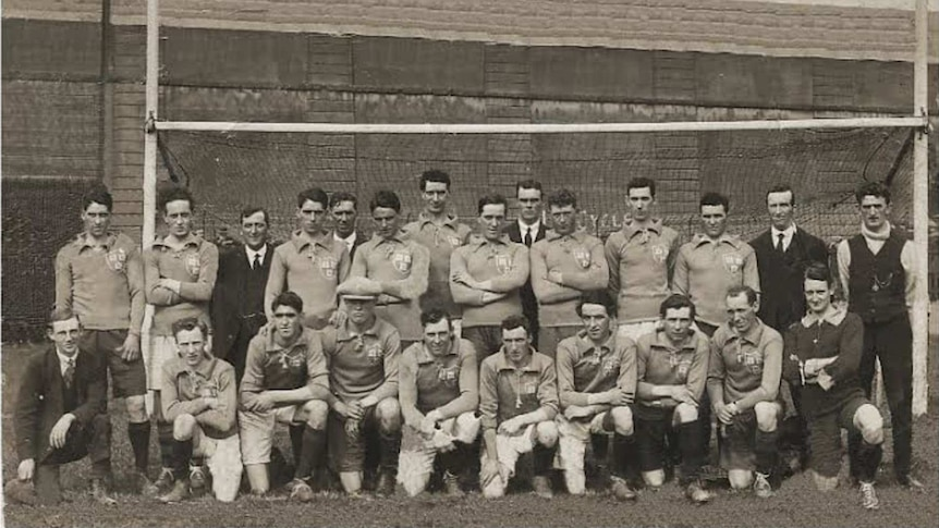 A sepia-tinted black and white photo of a group of men posing in front of some goal posts