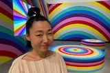 Japanese-Australian women stands in front of a room with walls, furniture and Tv screen covered in giant rainbows