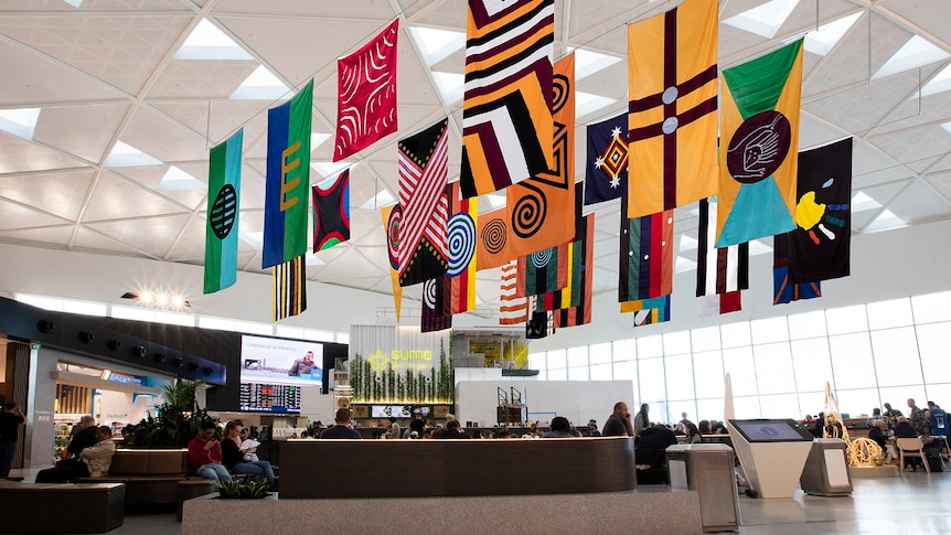 28 large flags by artist Archie Moore hanging from the ceiling of T1 International terminal.