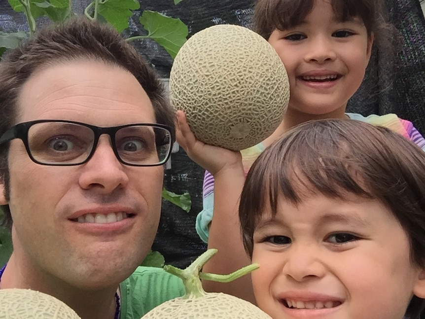 Australian journalist Scott McIntytre, wearing glasses, looks at the camera with his two children. They are holding rockmelons.