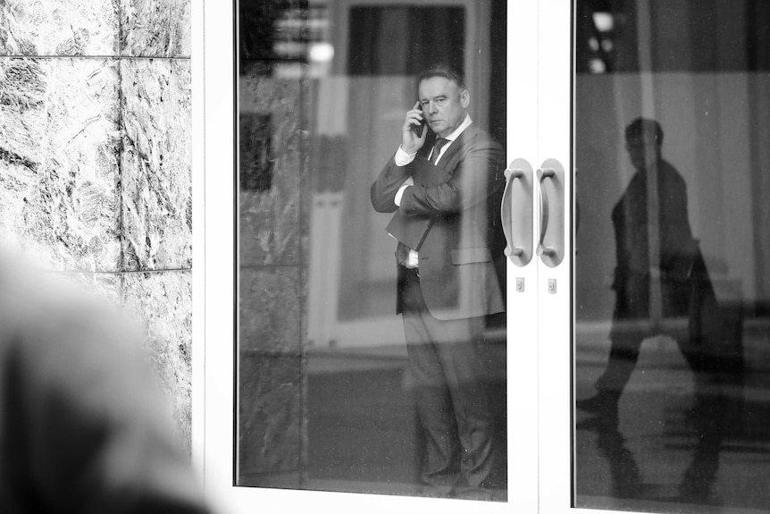 Joel Fitzgibbon looks out the window while speaking on his mobile phone