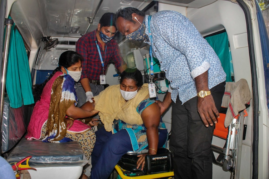 A woman is assisted by others to get down from an ambulance at hospital