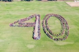 A large group of young people dressed in maroon, grey and white standing together to form the number 40 on a school oval.