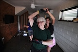 Ms Peatling dances with friends who helped her clean up her flooded Townsville home.