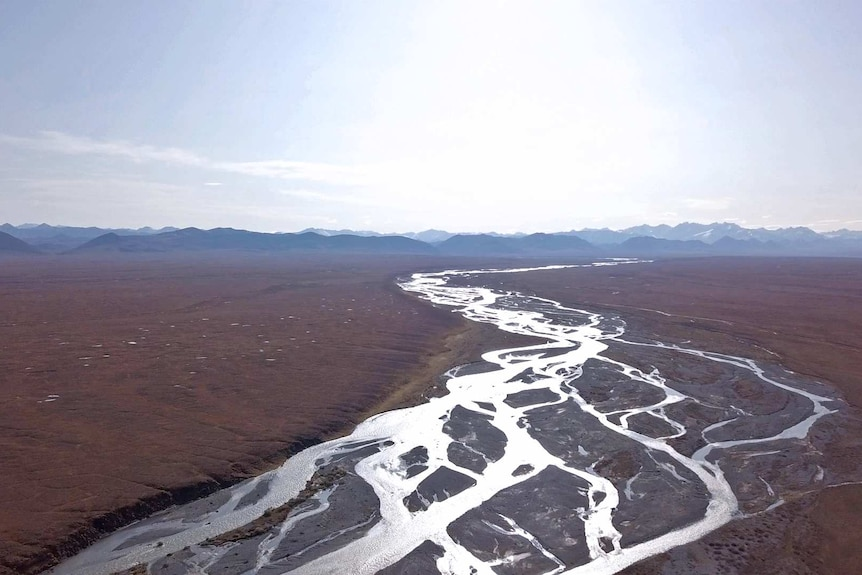 A river winds through a wide tundra with mountains in the distance.