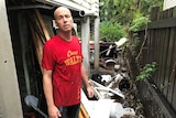 Frans Vogels stands next to debris that was washed out from under his house by storm water