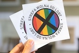 A hand is pictured holding two stickers with a black cross over a rainbow flag.