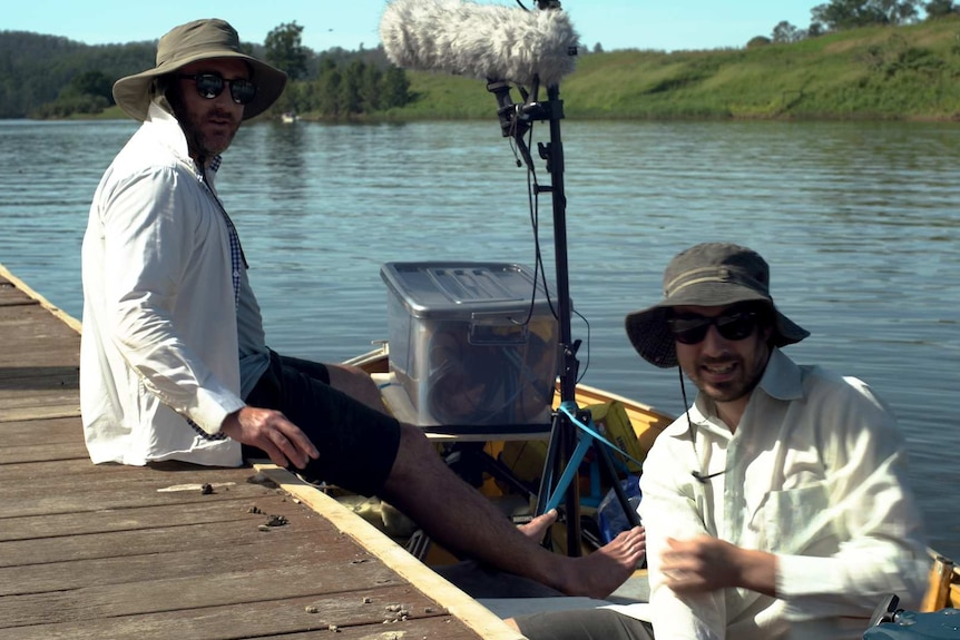 Two men in a boat with sound recording gear.