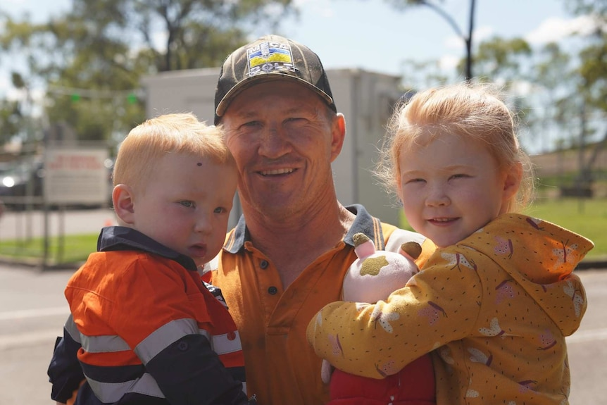 A man in a cap and high-vis smiles while holding two young kids.